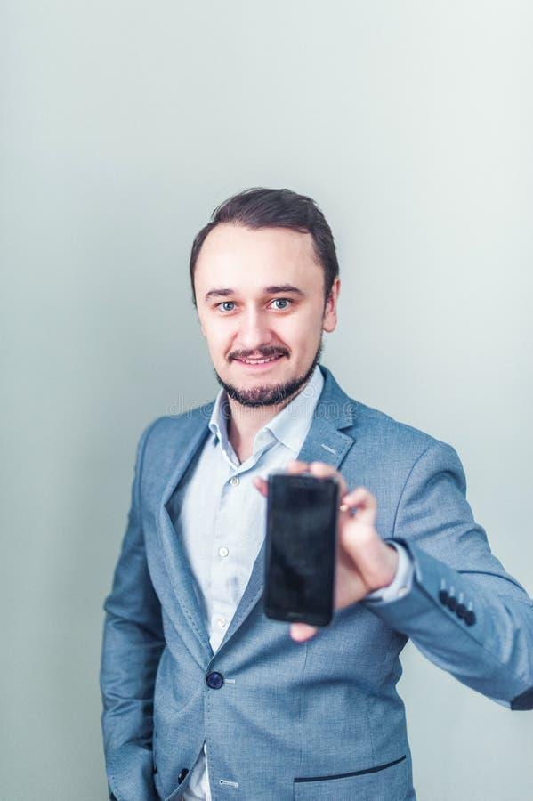 O homem no revestimento e com uma barba que mantém um telefone disponivel imagens de stock royalty free