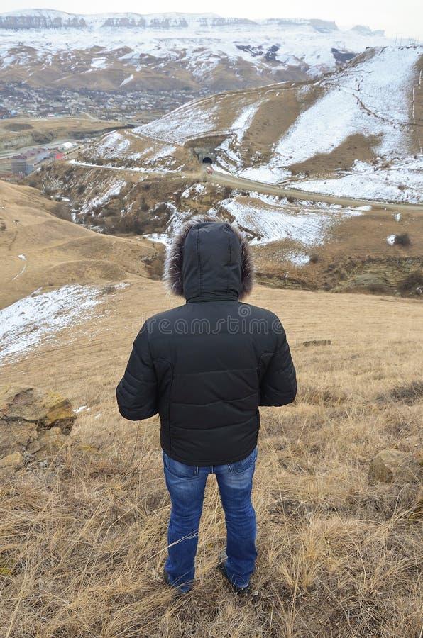 O homem no revestimento olha o desfiladeiro com montanhas imagens de stock royalty free