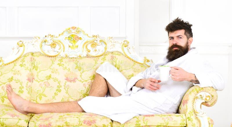 O homem no roupão bebe o café no hotel de luxo na manhã que olha a câmera Conceito luxuoso da vida O homem com barba aprecia imagens de stock