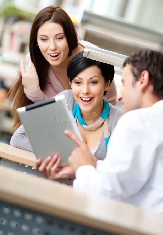 O homem no salão da leitura mostra a tabuleta a duas mulheres fotografia de stock