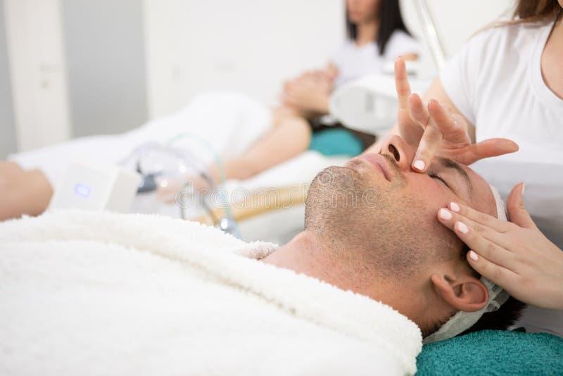 O homem no salão de beleza cosmético dos termas aprecia na massagem facial fotos de stock