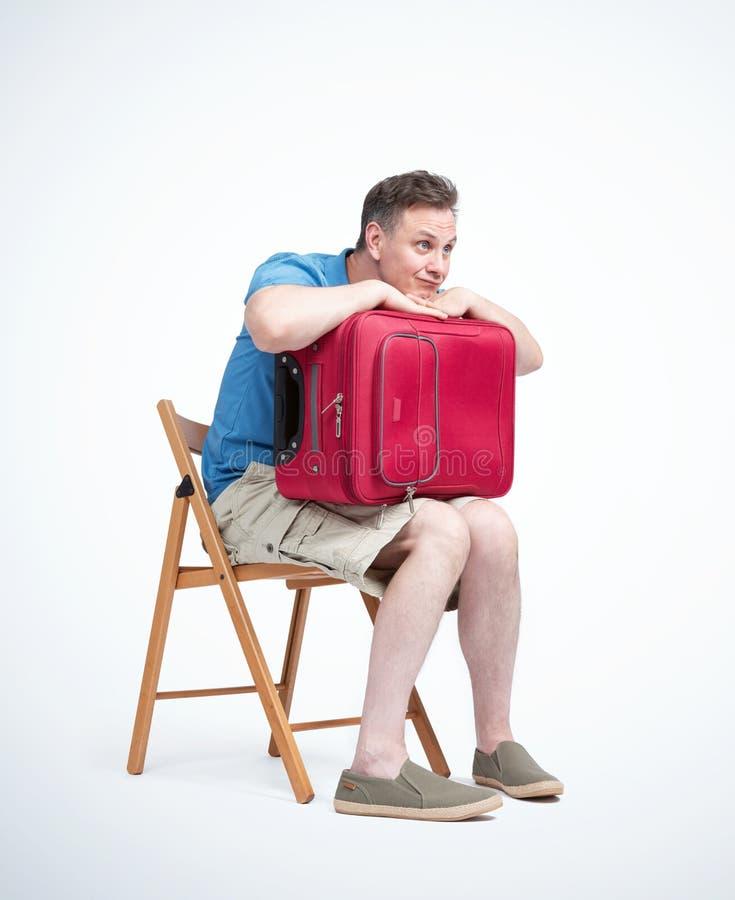 O homem no short e em um t-shirt com uma mala de viagem vermelha senta-se em uma espera da cadeira, isolada no fundo claro fotografia de stock