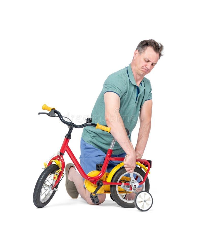 O homem no short e em um t-shirt está reparando uma bicicleta das crianças, nas mãos de uma chave Isolado no fundo branco imagem de stock