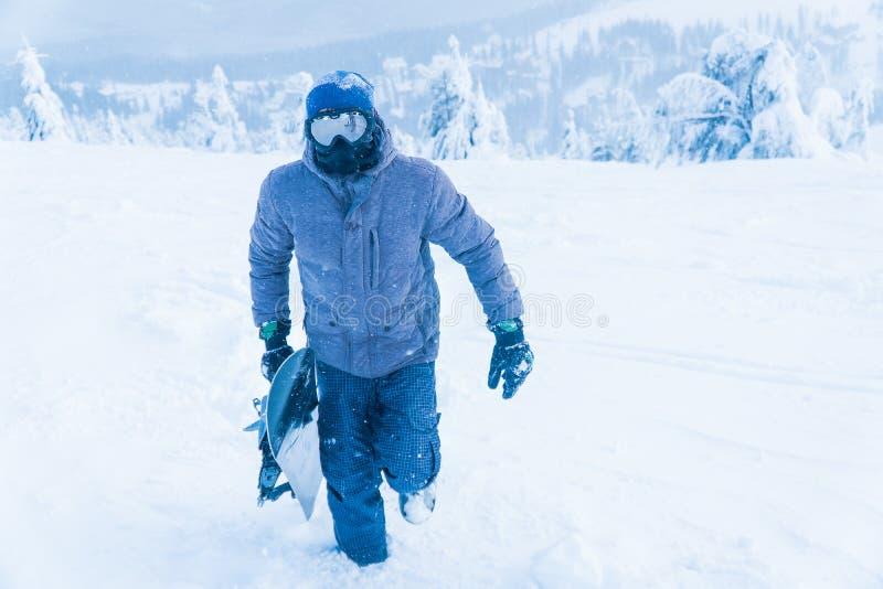O homem no snowboard da neve da montanha Homem que guarda uma placa fotos de stock