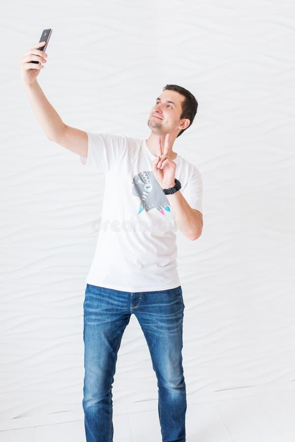 """O homem no t-shirt e na calças de ganga brancos faz o selfie em um fundo branco e mostra o gesto """"peace"""" foto de stock"""