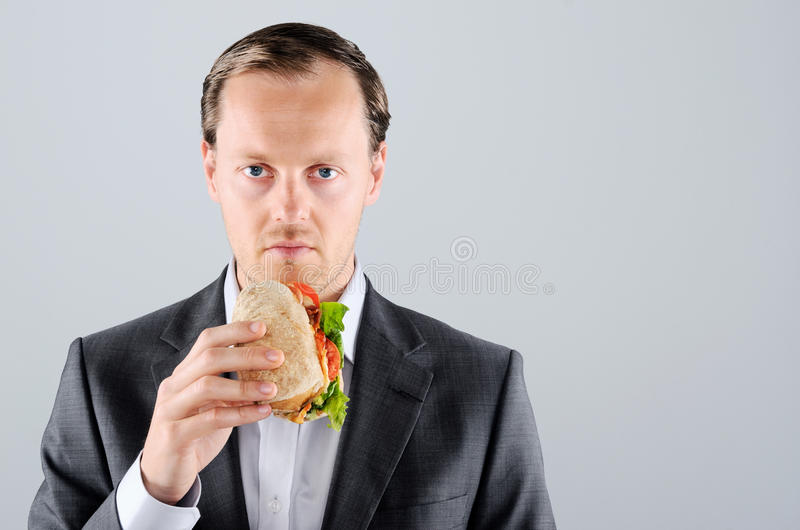 O homem no terno de negócio que come um delicioso leva embora o rolo de carne imagens de stock royalty free