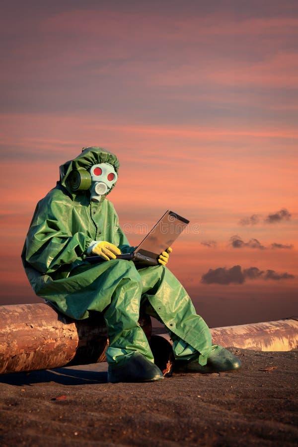 O homem no terno protetor trabalha na área da contaminação imagens de stock royalty free