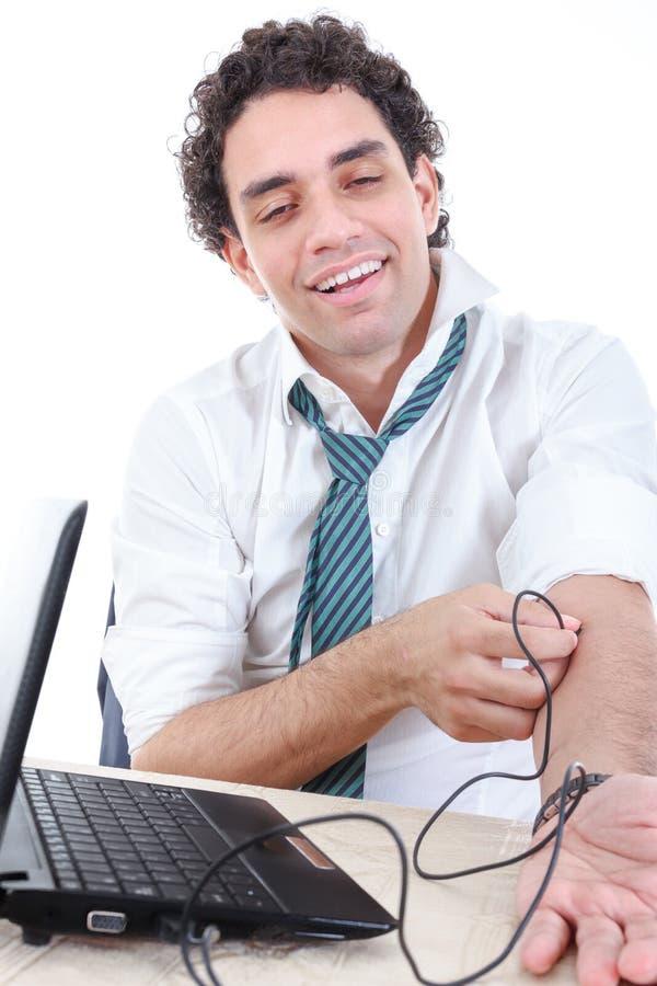 O homem no terno viciado ao Internet enrolou o cabo de USB dos comp(s) do portátil imagens de stock royalty free