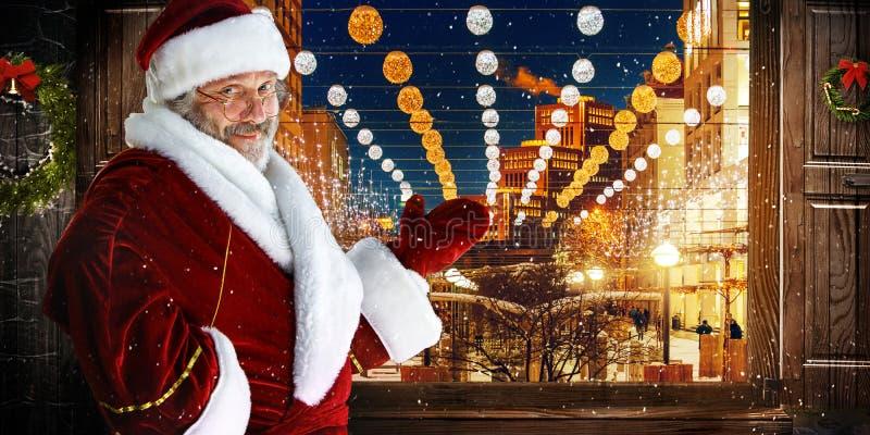 O homem no traje de Papai Noel sobre a cidade da noite fotografia de stock