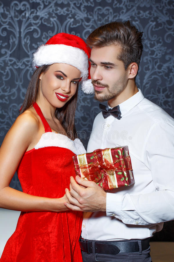 O homem no tux obtém o presente de Natal da amiga imagem de stock royalty free