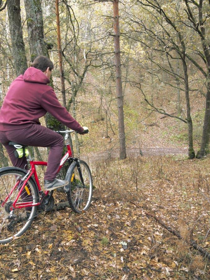 O homem no vermelho está indo rolar em uma bicicleta com uma inclinação íngreme no fotos de stock royalty free