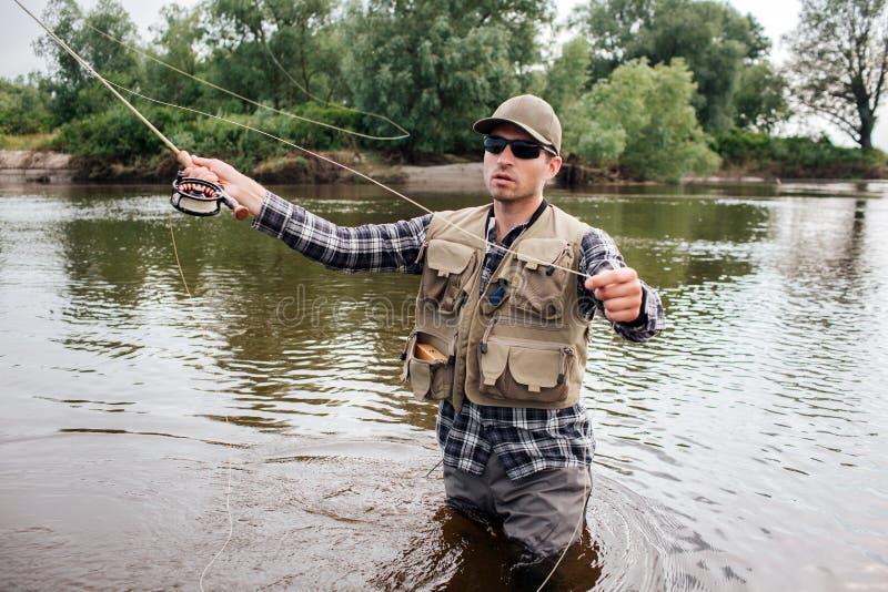 O homem nos óculos de sol está na água e na pesca Está preparando a pesca com mosca O indivíduo guarda-o em umas mão e colher no fotografia de stock royalty free