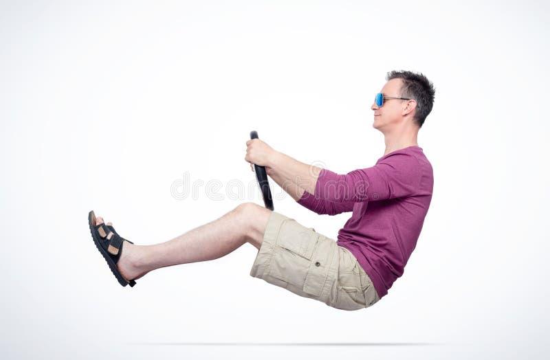 O homem nos óculos de sol, no short, no t-shirt vermelho e nas sandálias conduz um carro com um volante, no fundo claro r fotos de stock