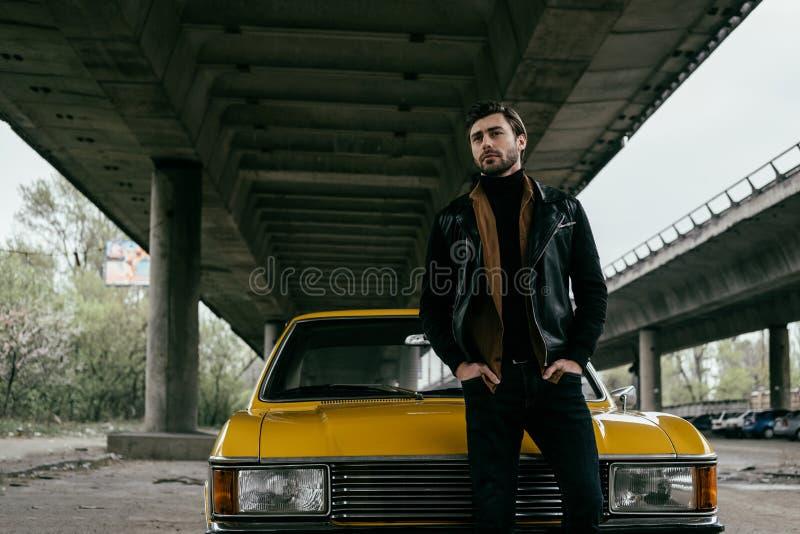 o homem novo à moda considerável no casaco de cabedal que está com mãos em uns bolsos aproxima o amarelo imagens de stock royalty free