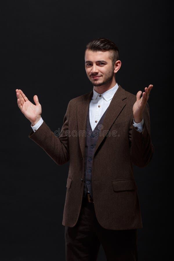 O homem novo à moda espalhou suas mãos em um fundo preto imagem de stock