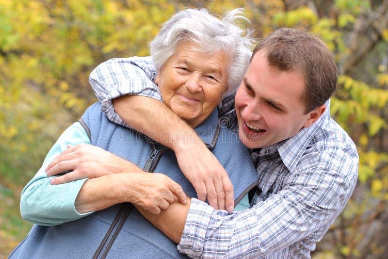 O homem novo abraça a mulher idosa imagens de stock