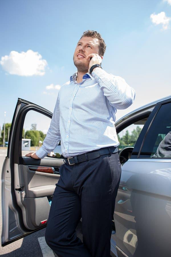 O homem novo alegre está comunicando-se perto do seu fotografia de stock royalty free