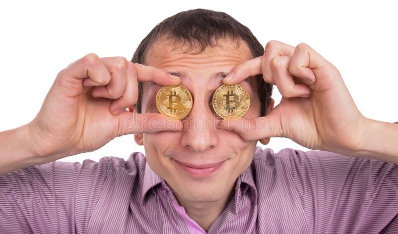 O homem novo alegre guarda o bitcoyne dois dourado nos olhos imagens de stock