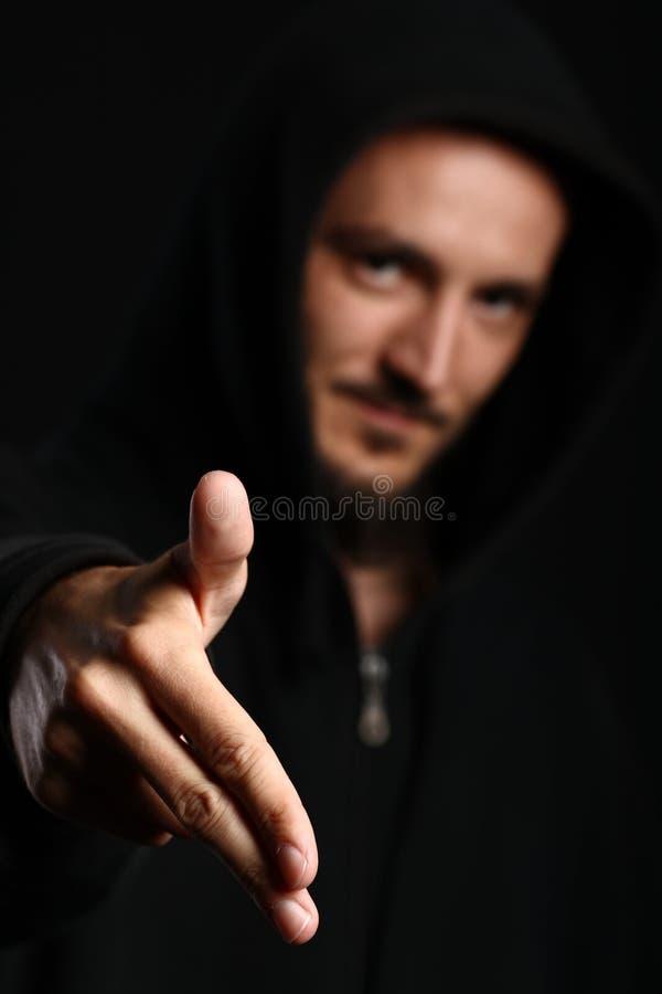O homem novo aponta seus dois dedos para a frente para baixo imagens de stock