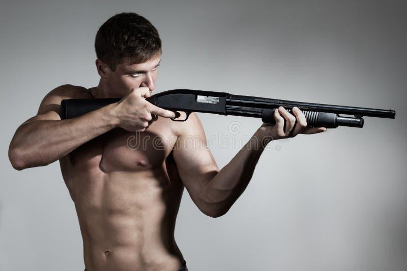O homem novo aponta uma arma imagens de stock royalty free