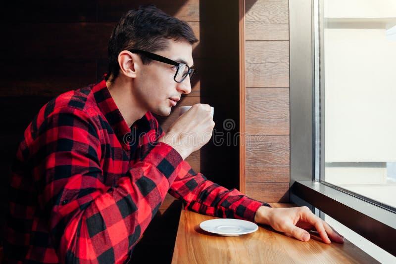 O homem novo aprecia o café no café na frente da janela imagem de stock
