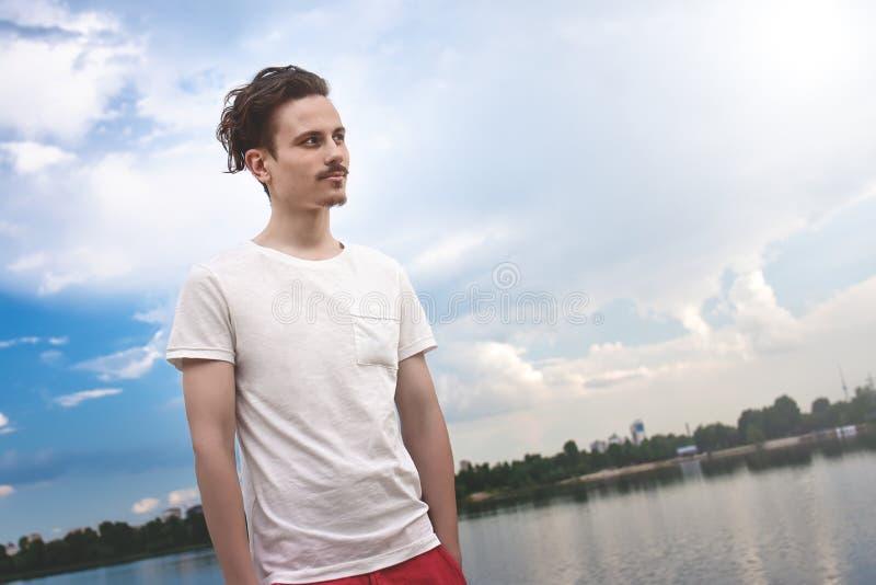 O homem novo aprecia uma vista bonita e olhares na distância perto de um lago e de uma floresta ver?o Mola nave imagem de stock royalty free