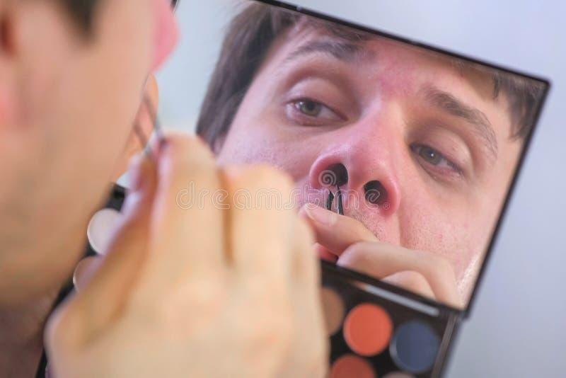O homem novo arranca seus cabelos do nariz com a pinça na frente do espelho em casa foto de stock royalty free