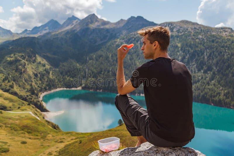 O homem novo assentado em uma rocha nas montanhas come a melancia e o olhar ao panorama imagem de stock