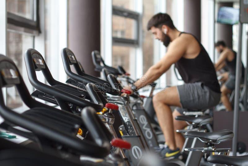 O homem novo atlético com uma barba é contratado em uma bicicleta estacionária no gym foto de stock