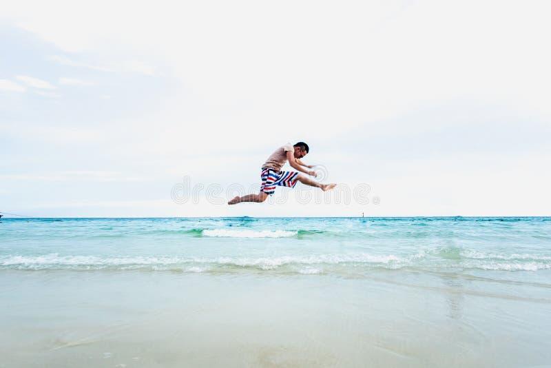 O homem novo atlético que aprecia o verão, saltando em um tropical seja fotografia de stock royalty free