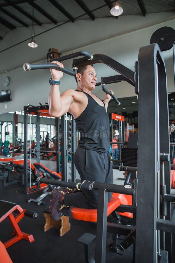 O homem novo atlético que exercita e que faz a tração levanta imagem de stock royalty free