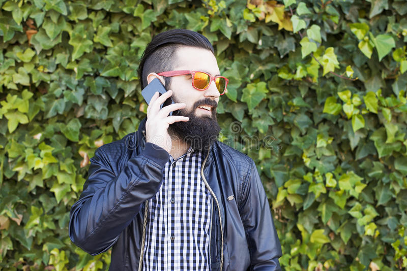O homem novo atrativo com barba fala no telefone imagens de stock