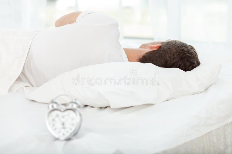 O homem novo atrativo está adormecido na manhã foto de stock royalty free
