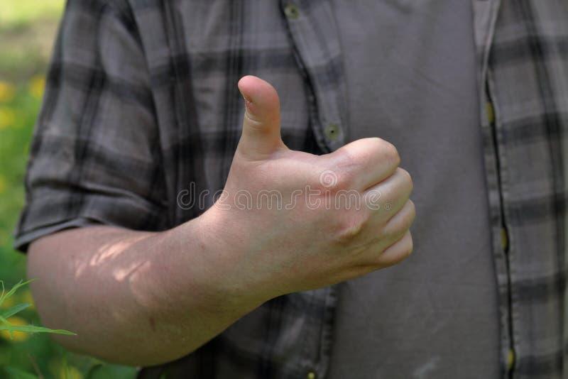 O homem novo aumentou acima um polegar As mostras gostam Close-up imagens de stock royalty free