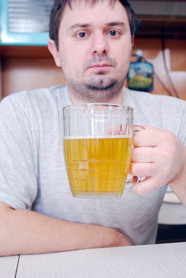 O homem novo bebe a cerveja na cozinha foto de stock royalty free