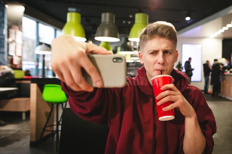 O homem novo bebe uma bebida de um vidro vermelho e faz um selfie foto de stock royalty free