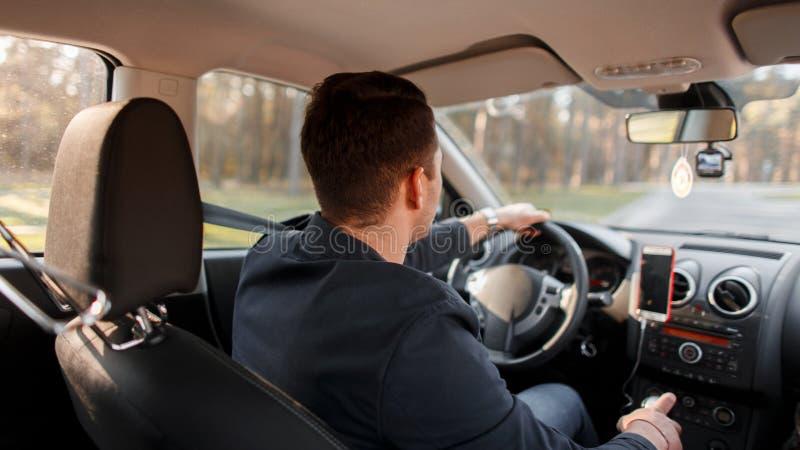 O homem novo bem sucedido conduz um carro em um dia ensolarado fotografia de stock