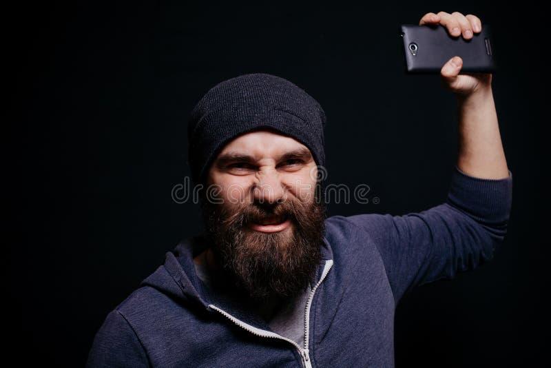 O homem novo bonito com uma barba faz o auto foto de stock royalty free