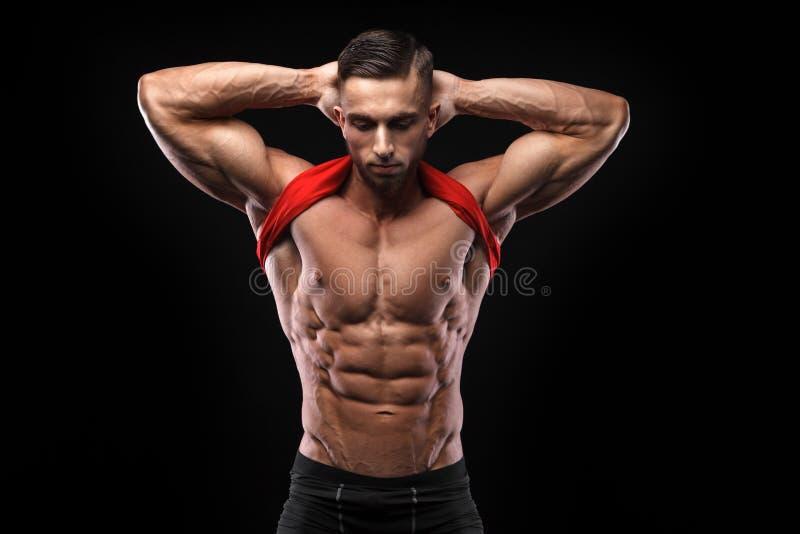 O homem novo bonito dos esportes no t-shirt vermelho mostra a relevo os músculos abdominais no gym foto de stock