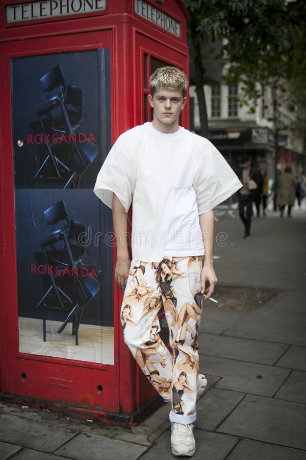 O homem novo bonito e à moda no t-shirt branco e no treinamento marrom colorido arfa na frente da cabine de telefone vermelha lev fotos de stock royalty free