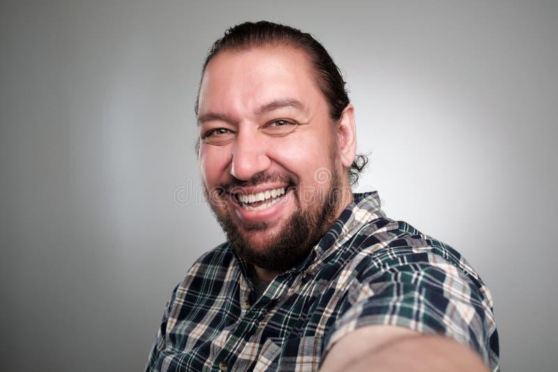 O homem novo bonito na roupa ocasional faz o selfie em um fundo cinzento Tem uma cara feliz, sorrindo com dentes fotos de stock royalty free