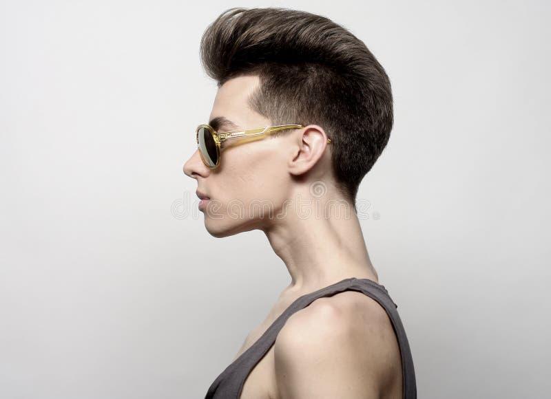 O homem novo bonito nos óculos de sol em um fundo branco Fas imagens de stock royalty free