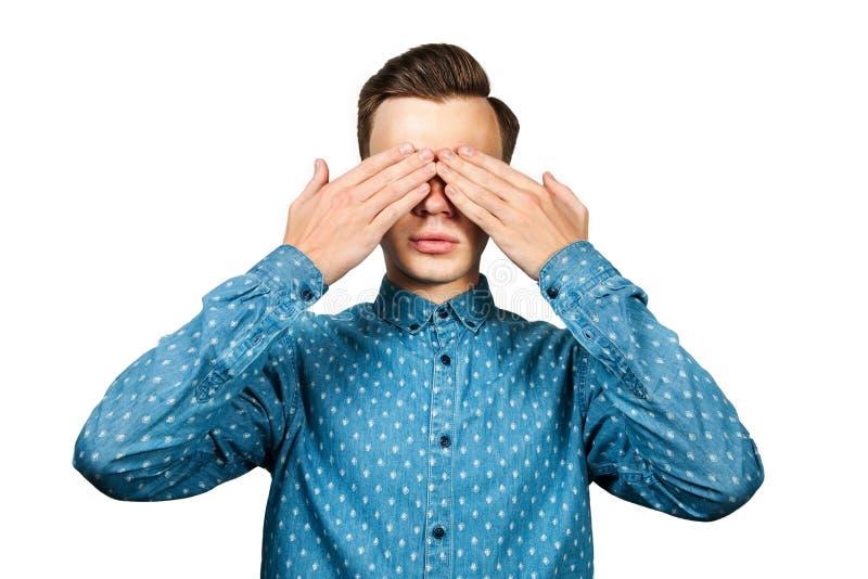 O homem novo branco do retrato vestido na camisa azul, fecha os olhos suas mãos Isolado no fundo branco fotografia de stock royalty free