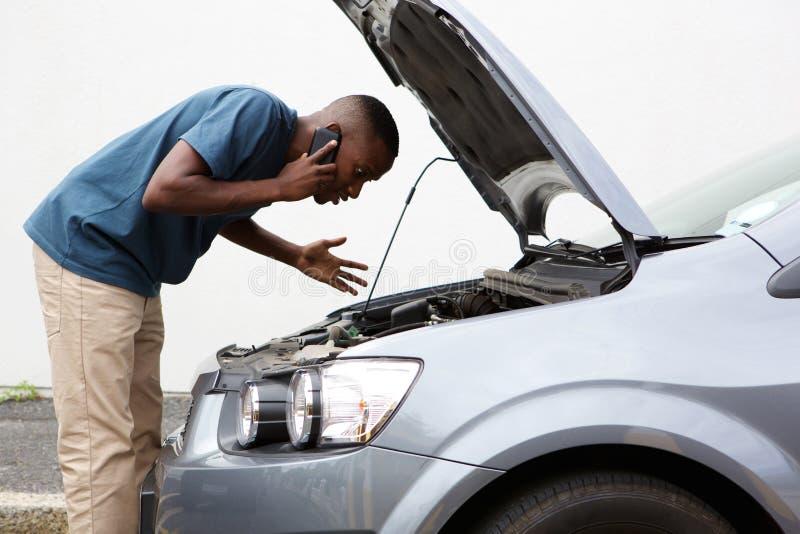 O homem novo chama para a ajuda com um carro parado imagens de stock royalty free