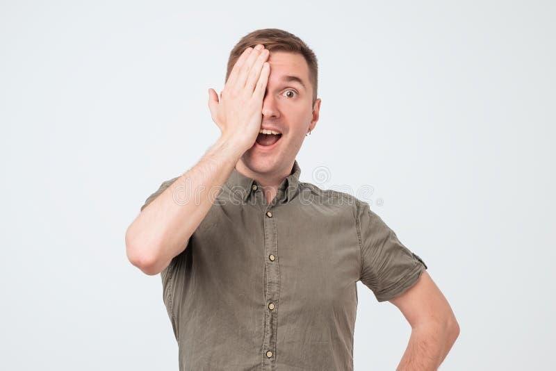 O homem novo cobre os olhos com as mãos, não vê claramente imagens de stock royalty free
