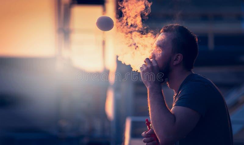 O homem novo com a barba no céu obscuro do por do sol do fundo, fazendo bolhas de sabão fuma para dentro com o auxílio do vape imagens de stock royalty free