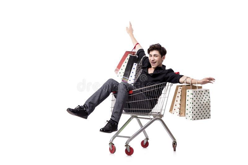O homem novo com carrinho de compras e sacos isolados no branco imagens de stock royalty free