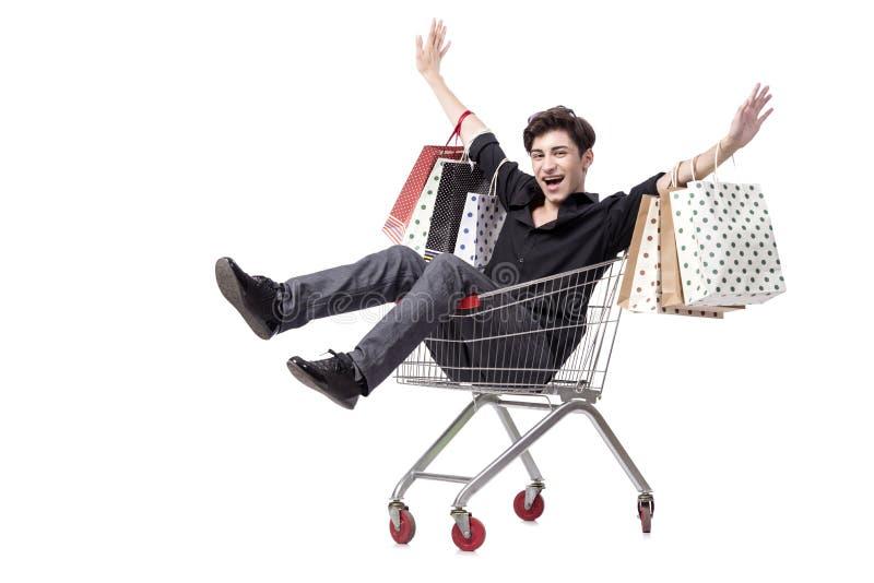 O homem novo com carrinho de compras e sacos isolados no branco foto de stock