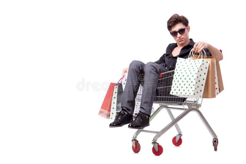 O homem novo com carrinho de compras e sacos isolados no branco imagem de stock