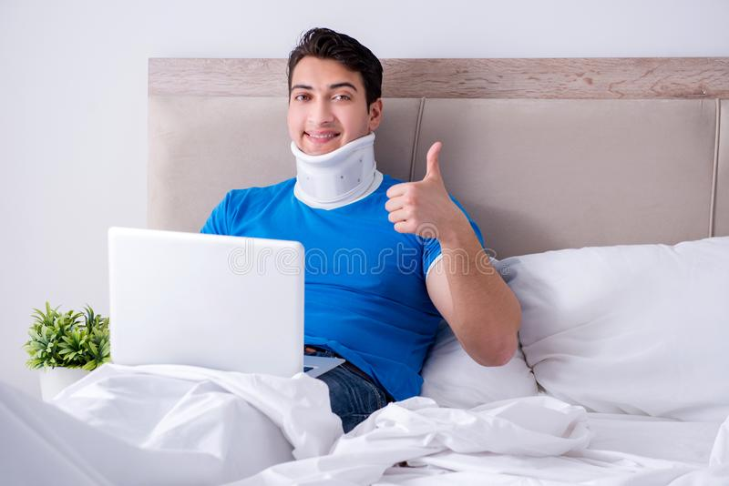 O homem novo com ferimento do pescoço na cama imagens de stock